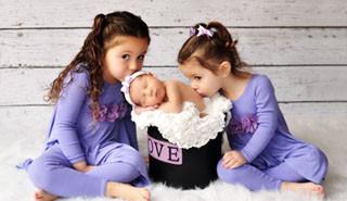 Twins kissing sleeping baby